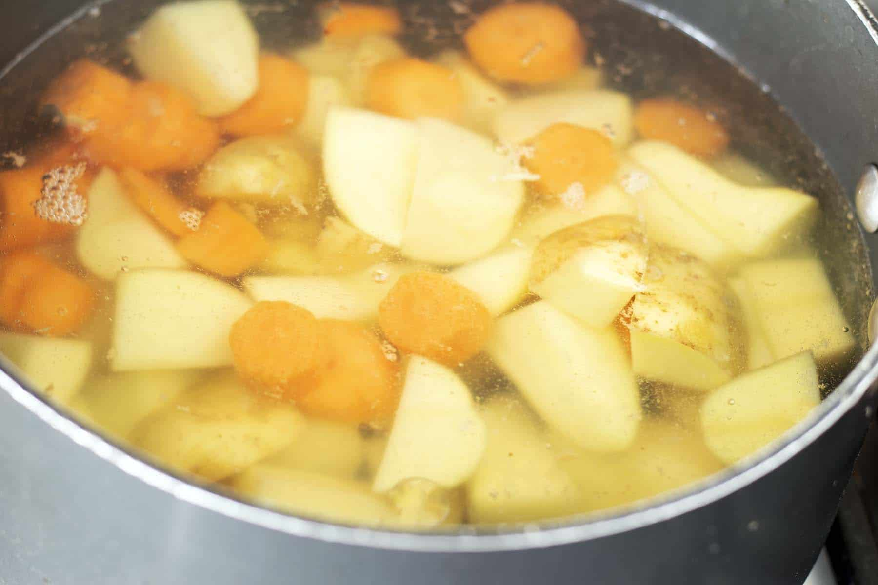 potatoes and carrots cooking in pan