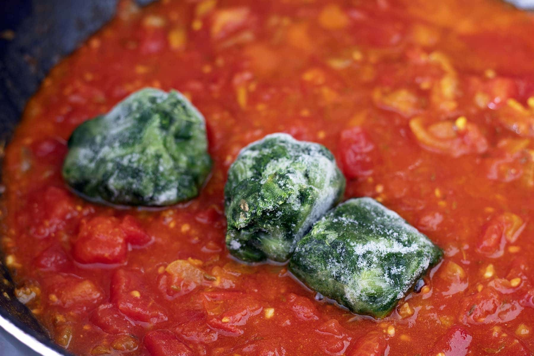 frozen spinach in pan with tomatoes