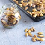 pumpkin seeds in glass year with baking tray in background