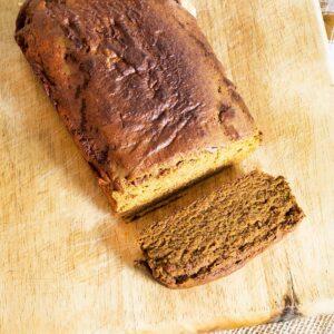 vegan pumpkin loaf cake on wooden chopping board