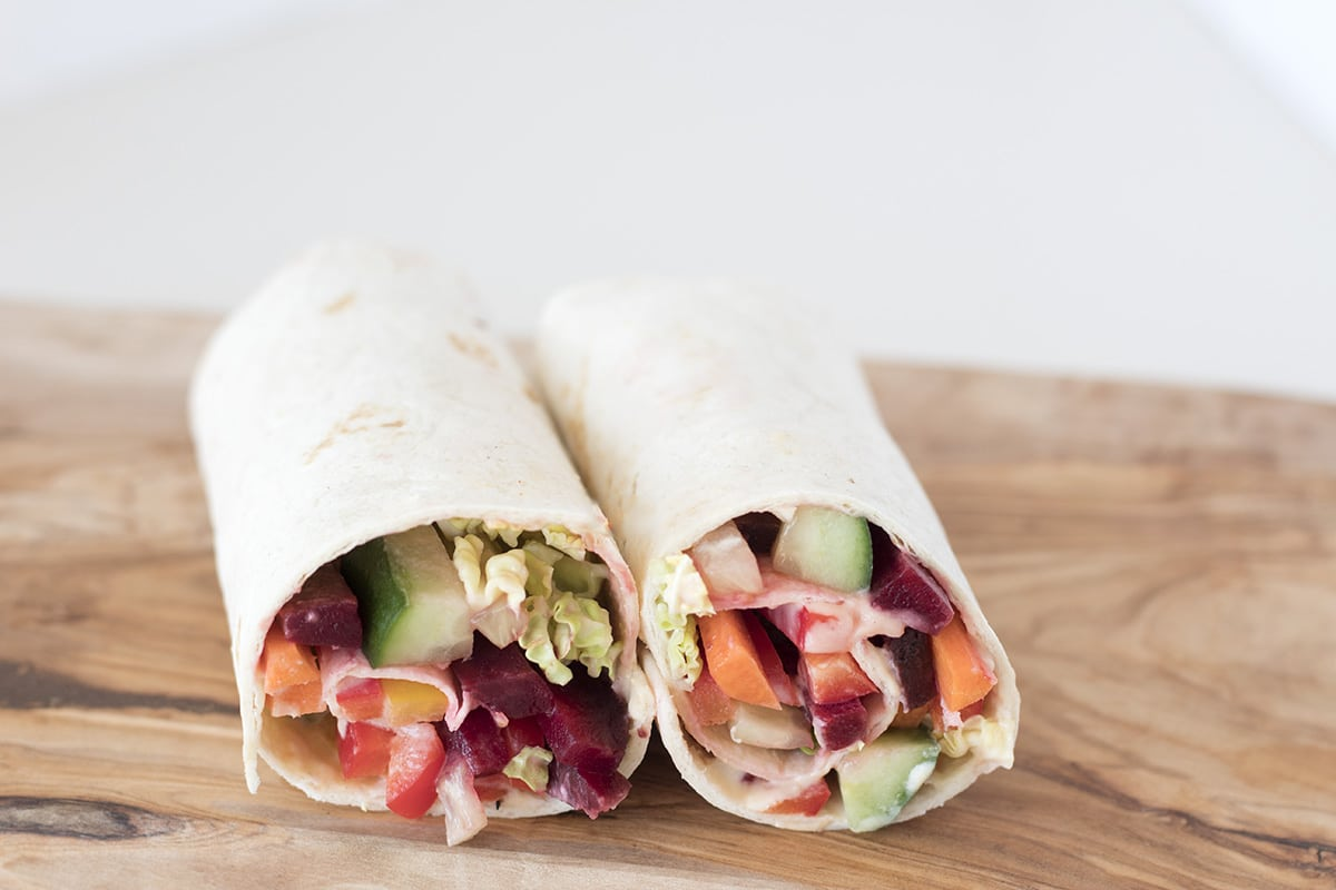 healthy tortilla wraps with rainbow vegetables on brown board