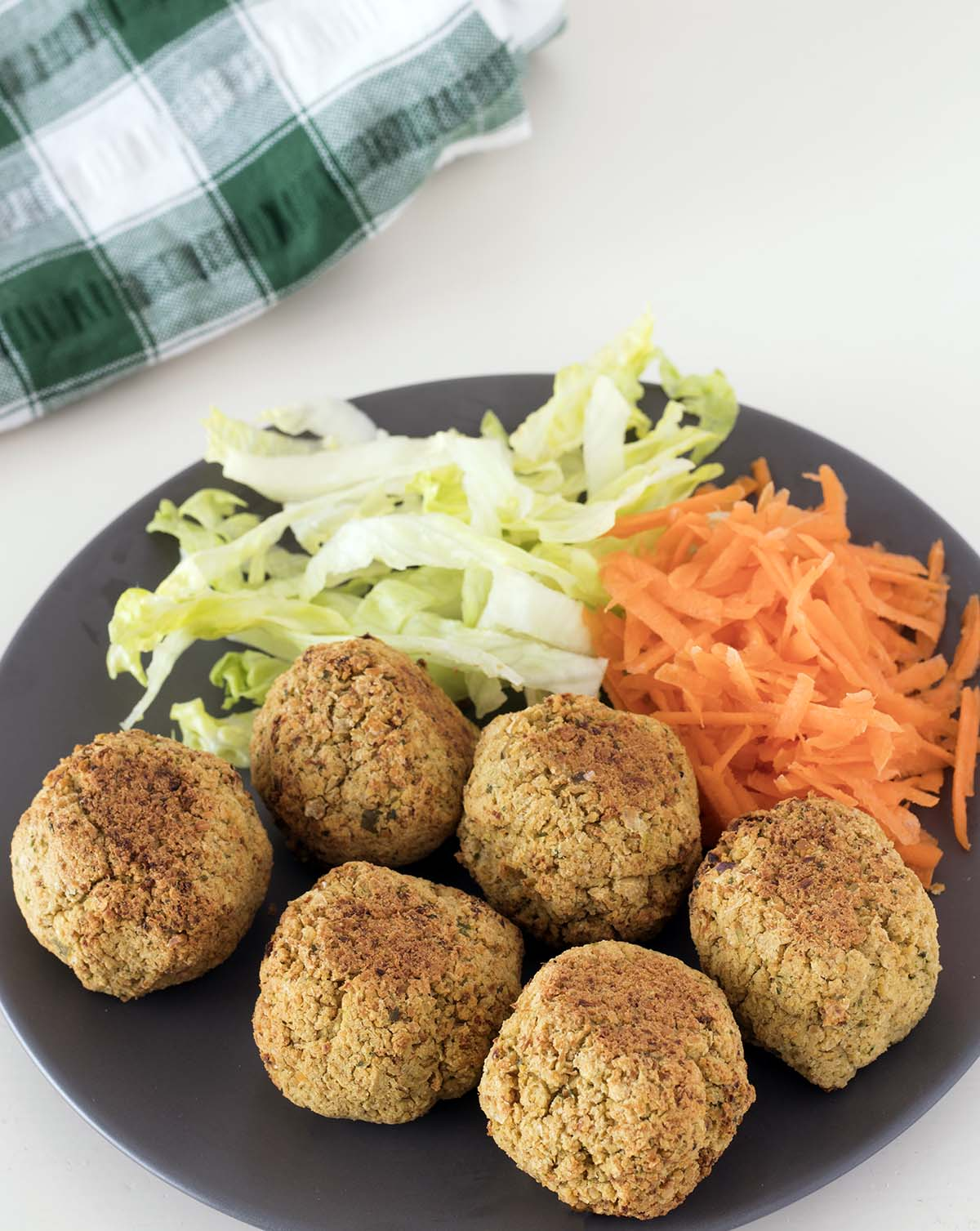 cauliflower falafel (baked) on plate with shredded lettuce and grated carrot