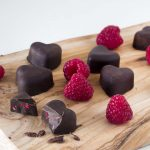 Vegan raspberry and chocolate hearts on wooden board