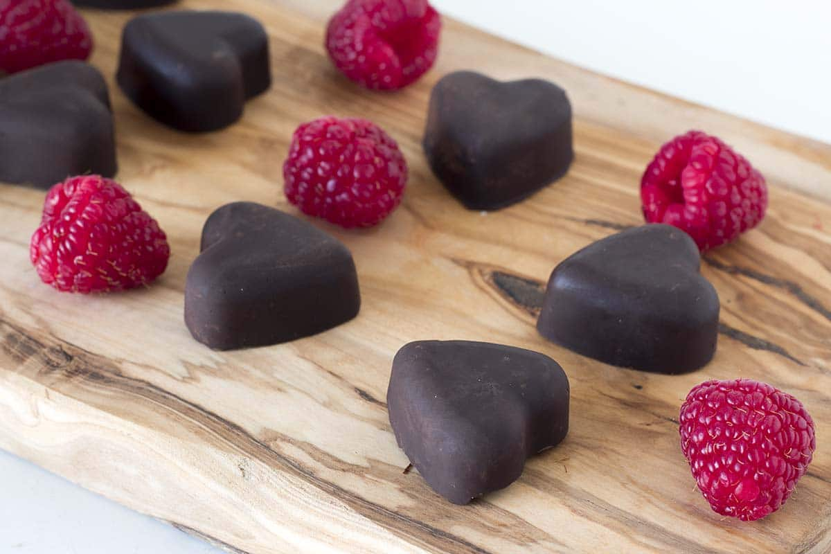 chocolate raspberry hearts on wooden board