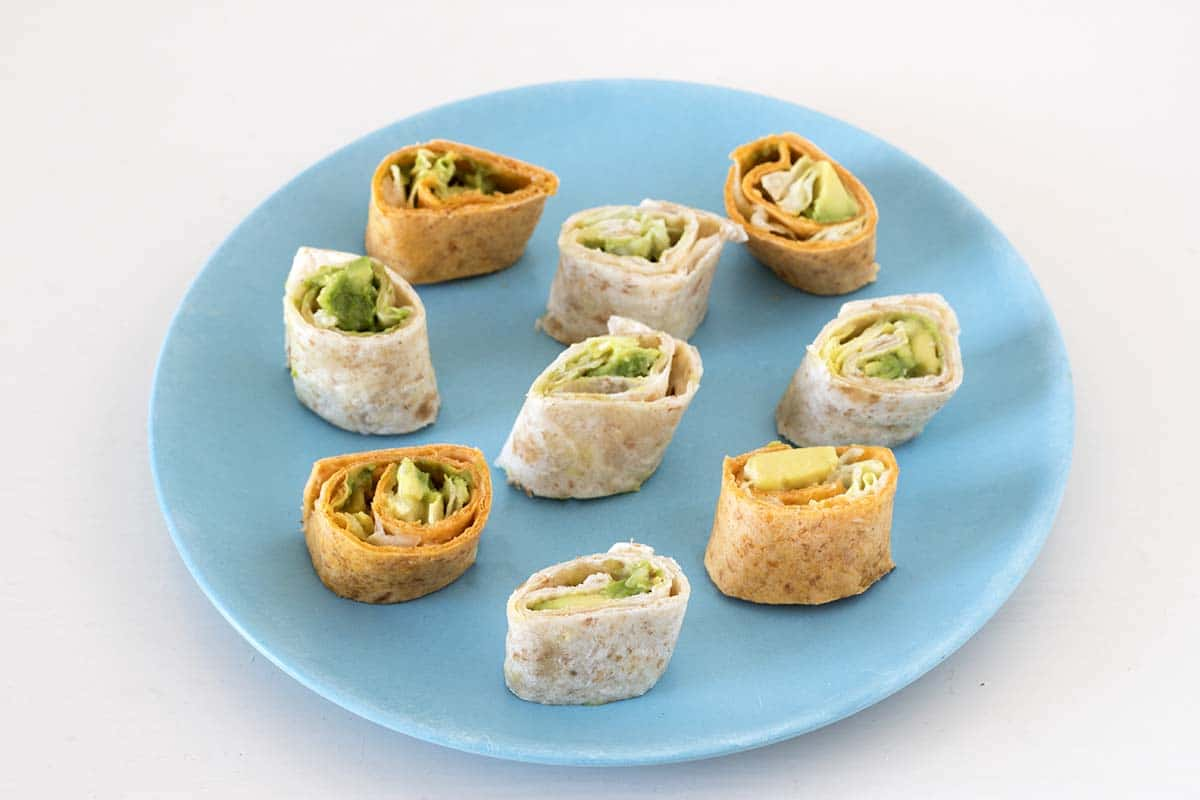 avocado, hummus and lettuce wrap pinwheels on blue plate