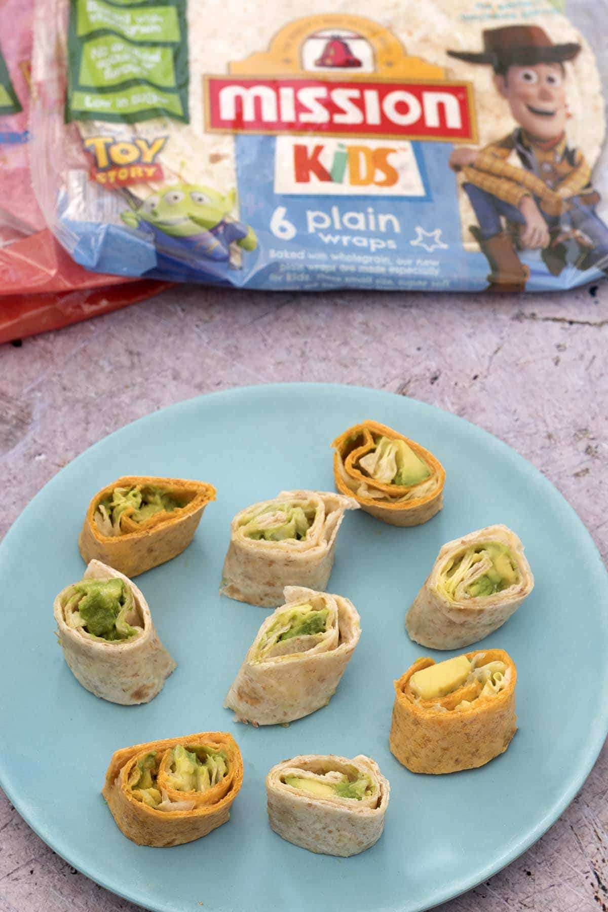 tortilla pinwheels on blue plate with mission deli wraps