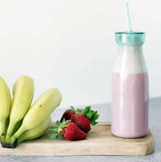 healthy strawberry milkshake in bottle with fresh bananas and strawberries on board