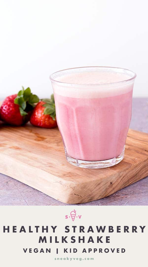 healthy strawberry milkshake in glass with strawberries on wooden board in background