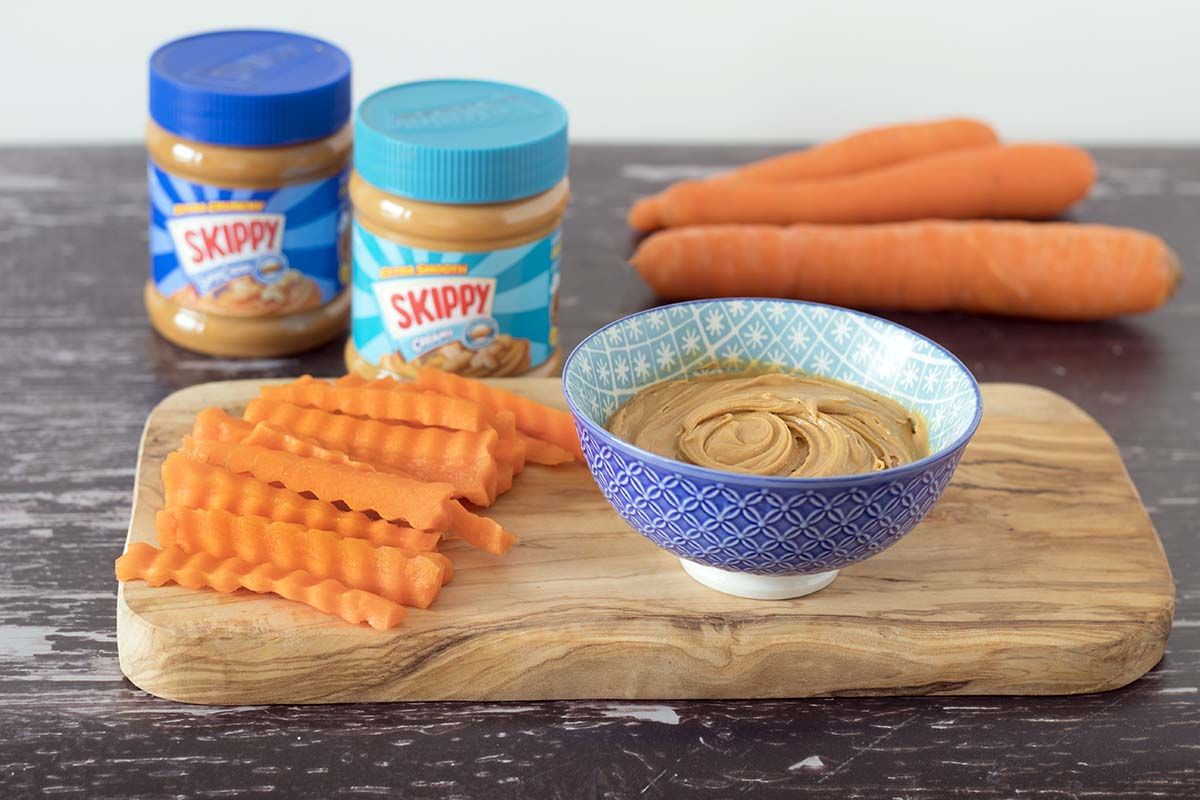 carrots and peanut butter on wooden board with Skippy peanut butter in jar