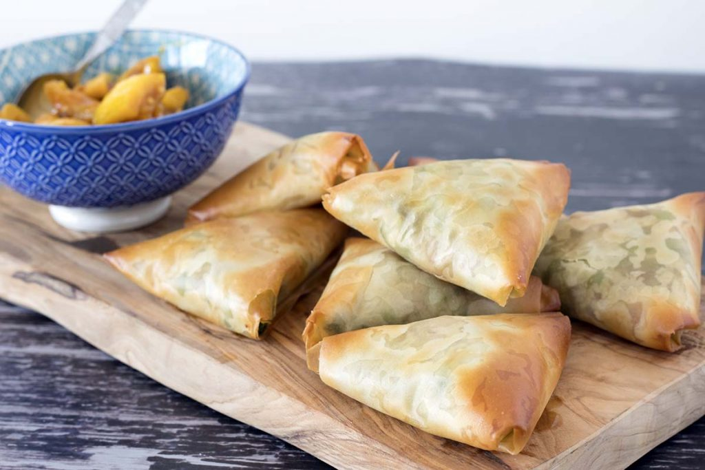 Baked samosas made with filo pastry on wooden board with blue bowl in background