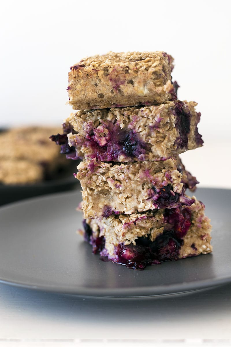 close up of blueberry banana porridge bars stacked up on grey plate