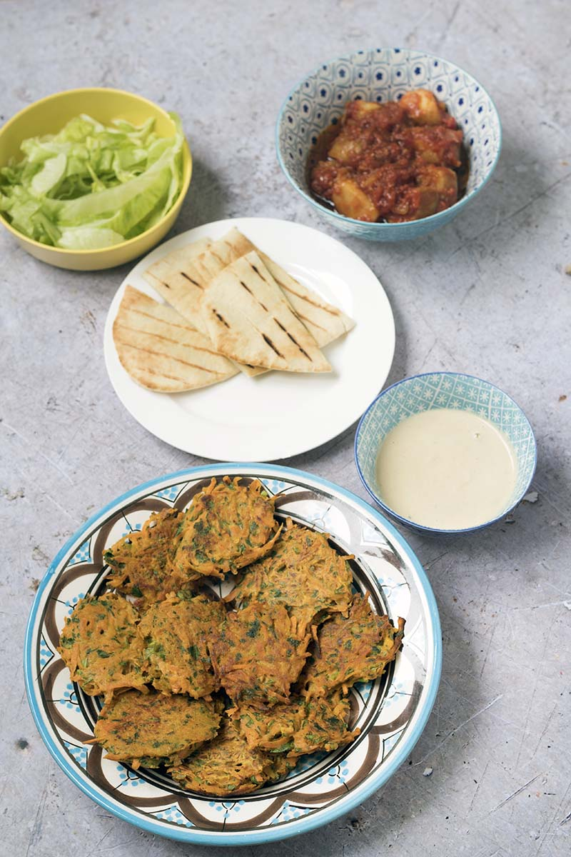 cooked carrot fritters, pitta bread, tahini, patatas bravas and lettuce in bowls on grey background