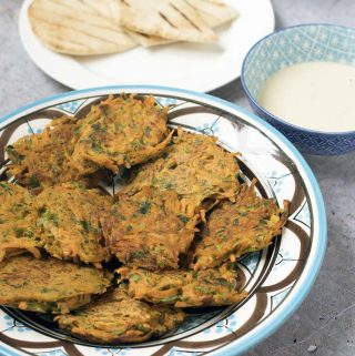 Carrot and herb fritters on plate with tahini and pitta