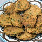 close up of vegan carrot fritters on blue and white bowl