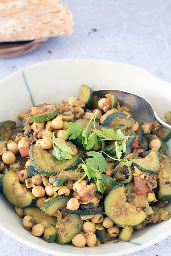 chickpea and courgette curry with flatbreads in background