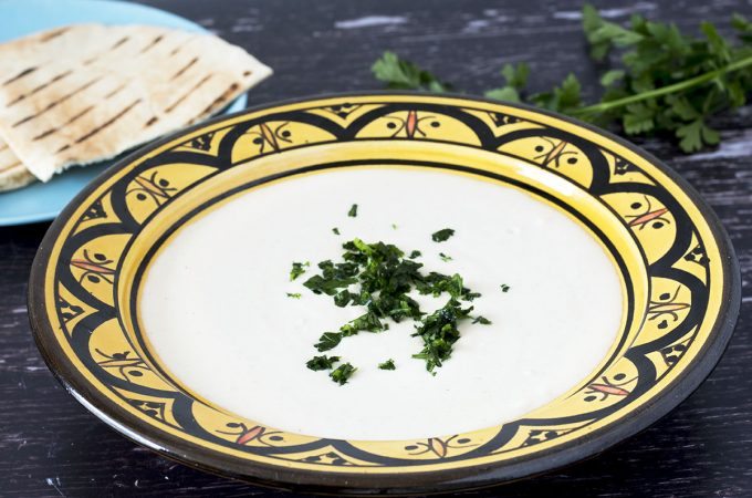 healthy garlic tahini sauce in yellow bowl with pitta and herbs in background