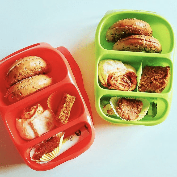 Red and green Goodbyn lunchboxes filled with healthy food for kids