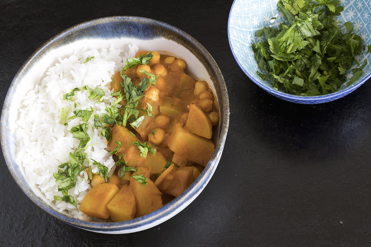 potato and chickpea curry with rice and chopped coriander