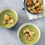 courgette and potato soup with croutons on grey background