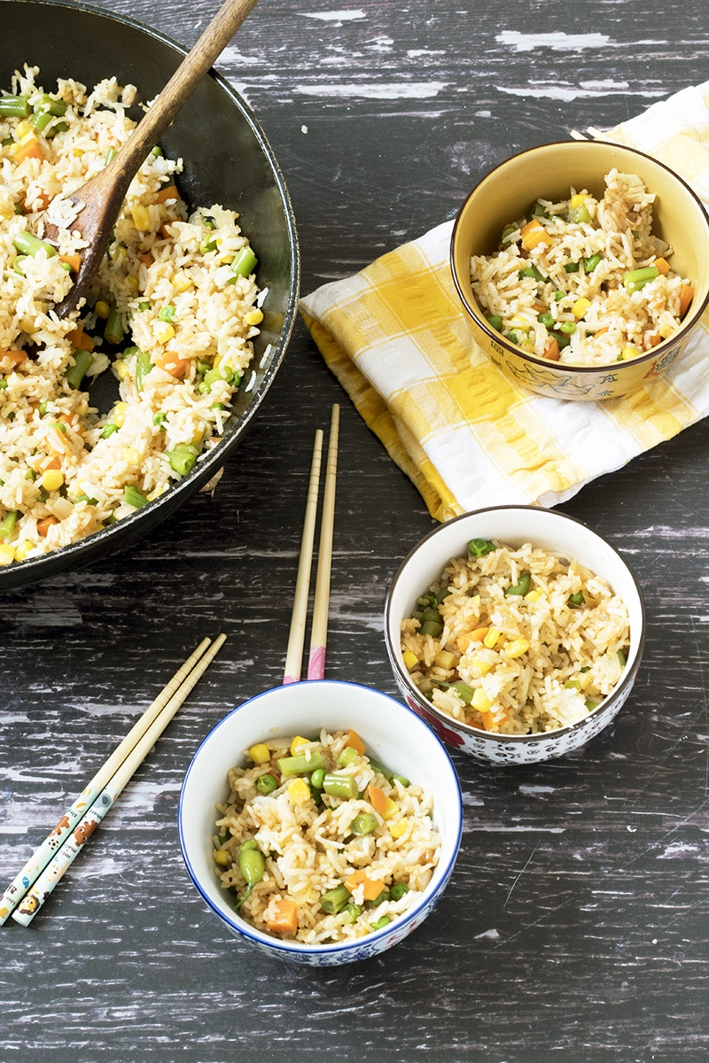 veggie fried rice in bowls and wok with wooden background