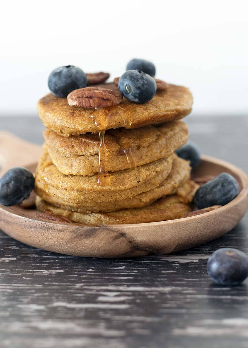 healthy butternut or pumpkin pancakes in stack with blueberries, maple syrup and pecan nuts