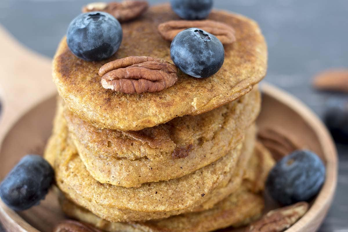 CLOSE UP OF butternut squash pancakes with blueberries and pecan nuts