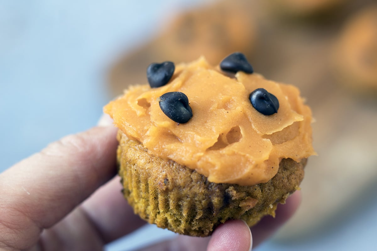 hand holding healthy pumpkin muffin with sweet potato frosting