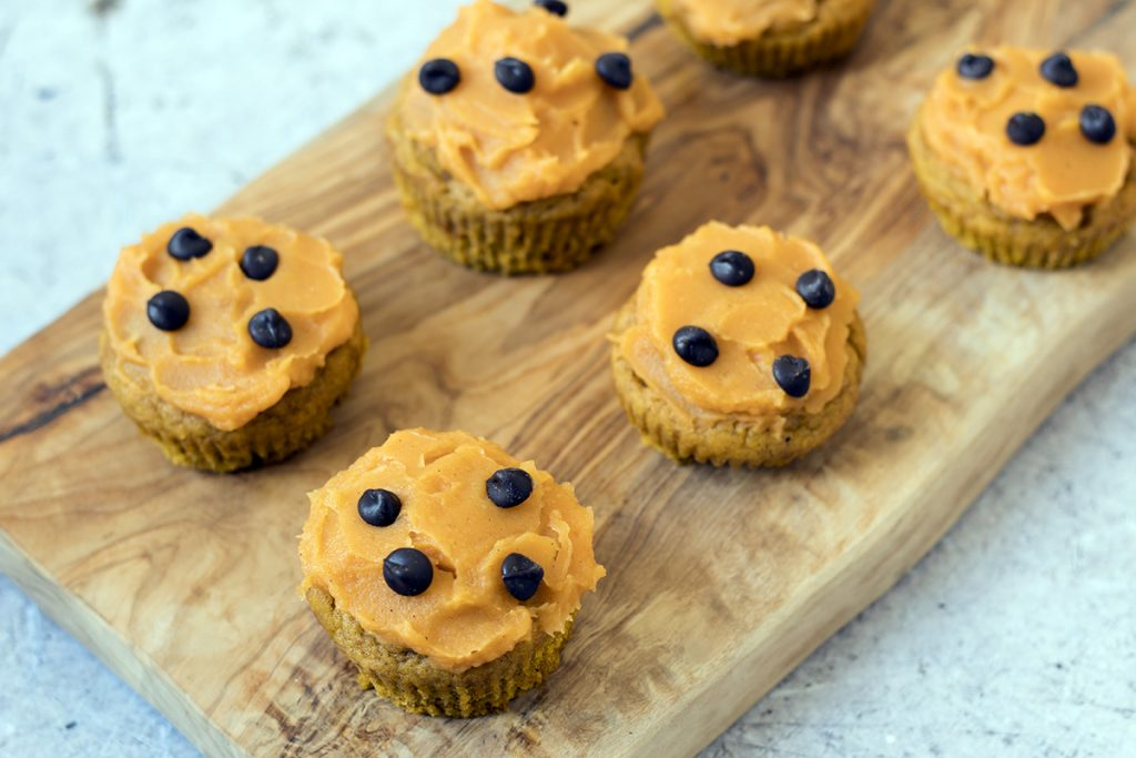 healthy pumpkin muffins with sweet potato frosting on wooden board
