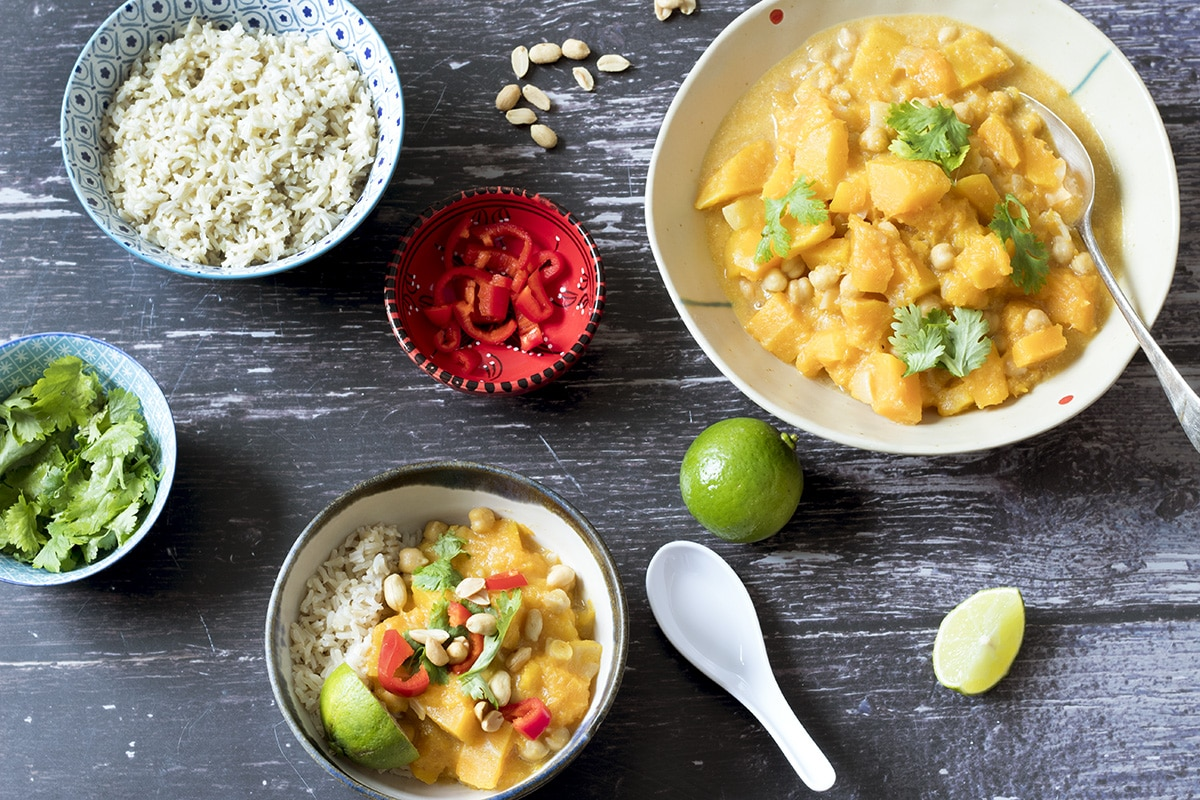 thai pumpkin curry with rice, chillies, lime and peanuts on brown backgroun
