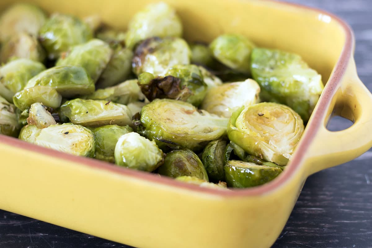 close up of garlic roasted brussels sprouts in yellow baking dish