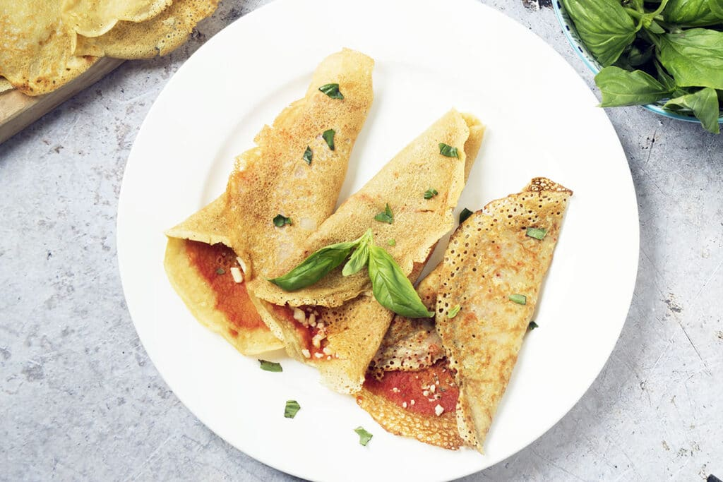 overhead shot of pizza pancakes on white plate