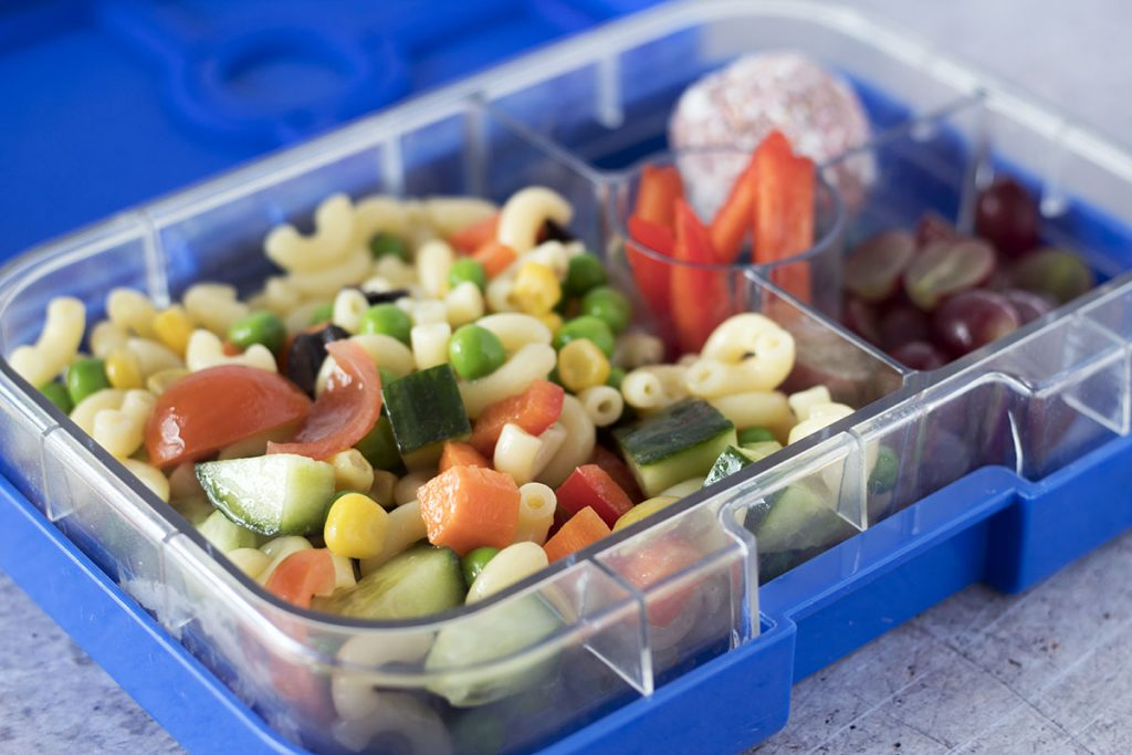 blue lunchbox with healthy pasta salad, energy ball, peppers and grapes