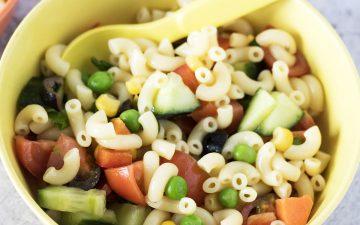 kids pasta salad in yellow and orange bowls