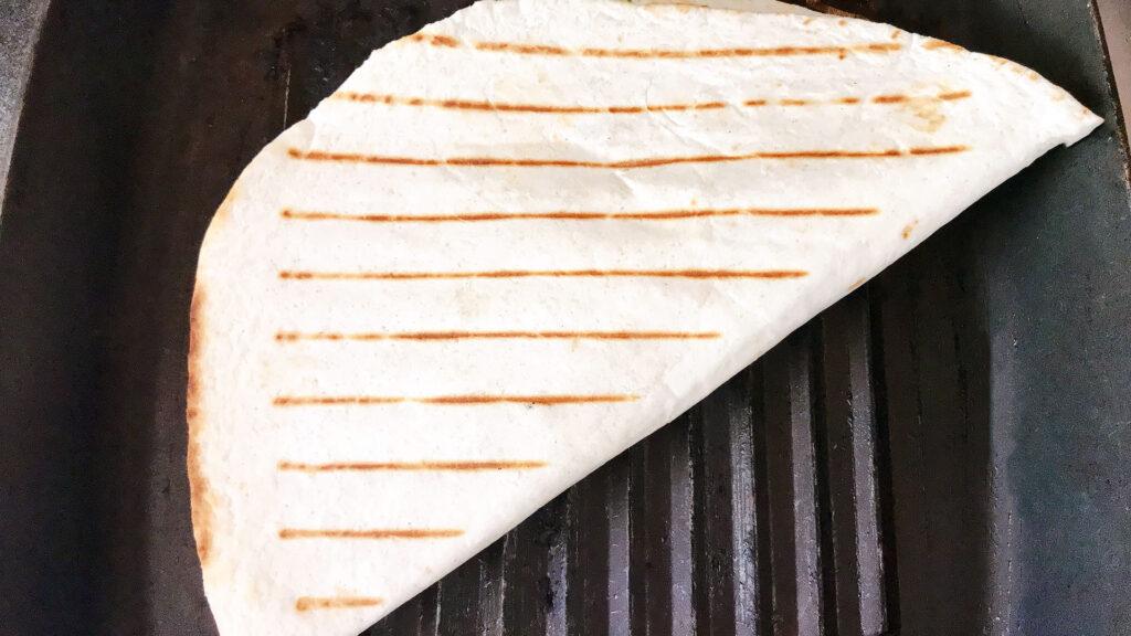 Folded quesadilla on griddle pan