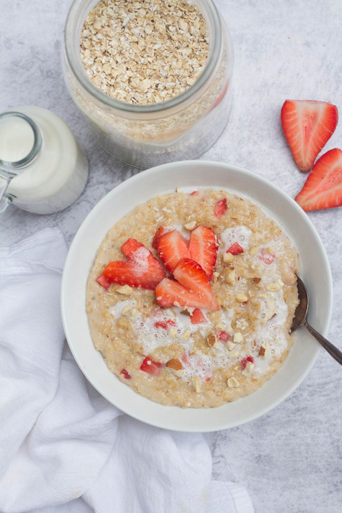 strawberry porridge in white bowl and ingredients