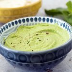 Pea and mint dip in blue bowl with mint sprigs and yellow bowl in background