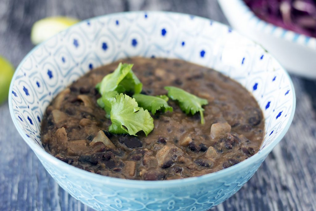 refried black beans in blue and white bowl with limes and cabbage salad
