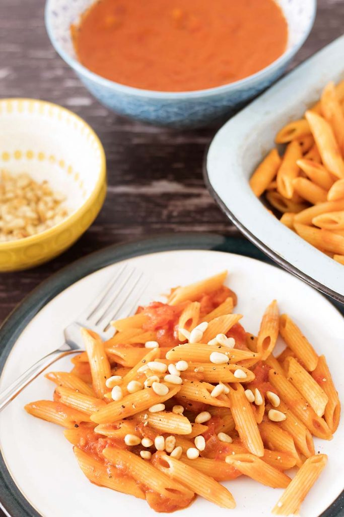 portrait image of creamy tomato sauce with pasta and pine nuts