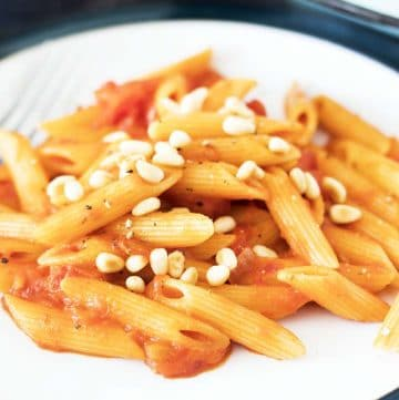close up shot of pasta with creamy tomato sauce and pine nuts on white plate