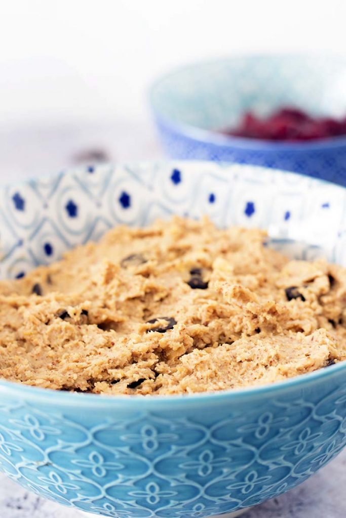 close up of chickpea healthy cookie dough in blue and white bowl with berries in background