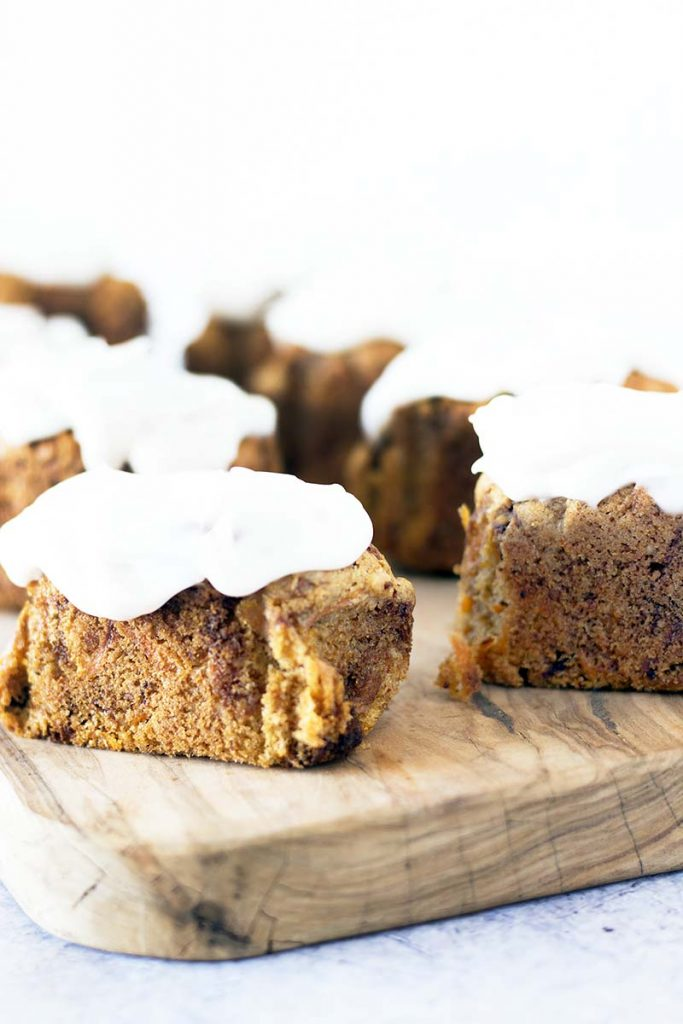two rows of mini carrot loaves on wooden board with frosting
