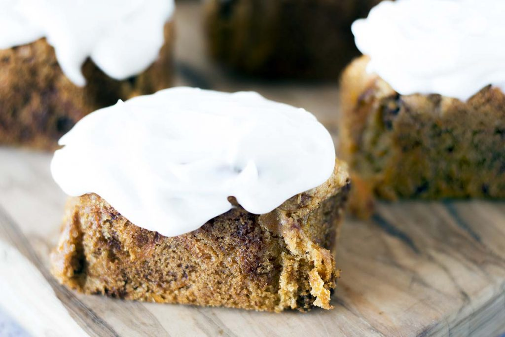 mini carrot cakes with frosting on wooden board