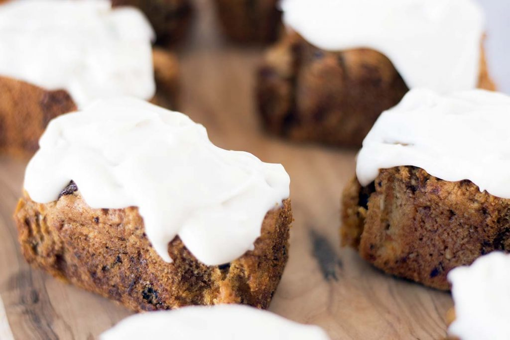 close up shot of mini carrot loaf cakes on wooden board
