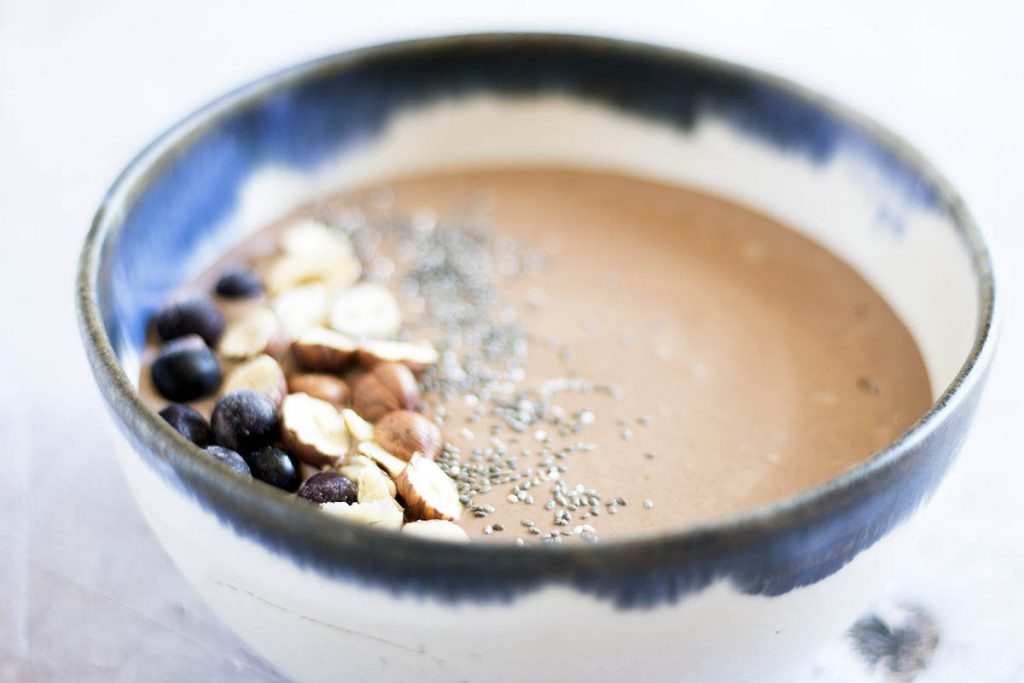 hazelnut and chocolate smoothie bowl in blue and white bowl with toppings