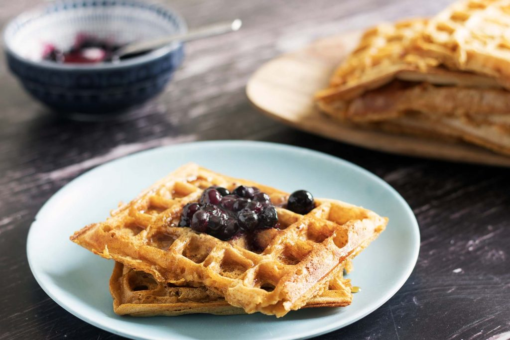 sweet potato waffles on blue plate topped with blueberries. Board in background with more waffles on and bowl of blueberries