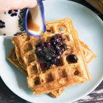 two sweet potato waffles on blue plate with blueberries and maple syrup being poured from jug