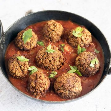 vegan meatballs in black dish with tomato sauce