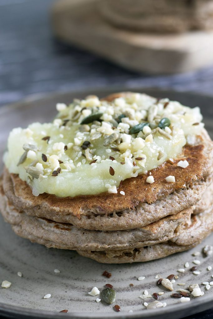 gingerbread pancakes in a stack with apple and seeds