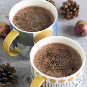 two mugs of healthy hot chocolate with christmas decorations in background