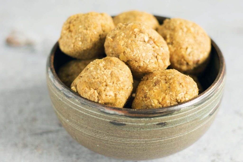 pumpkin and apricot energy balls in ceramic bowl on grey background